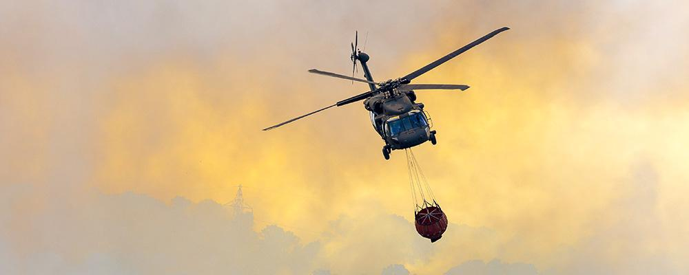 Helicopter carrying water to fire