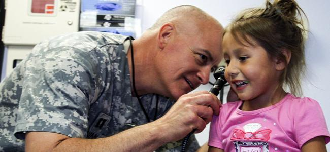 Army doctor examining little girl's ears